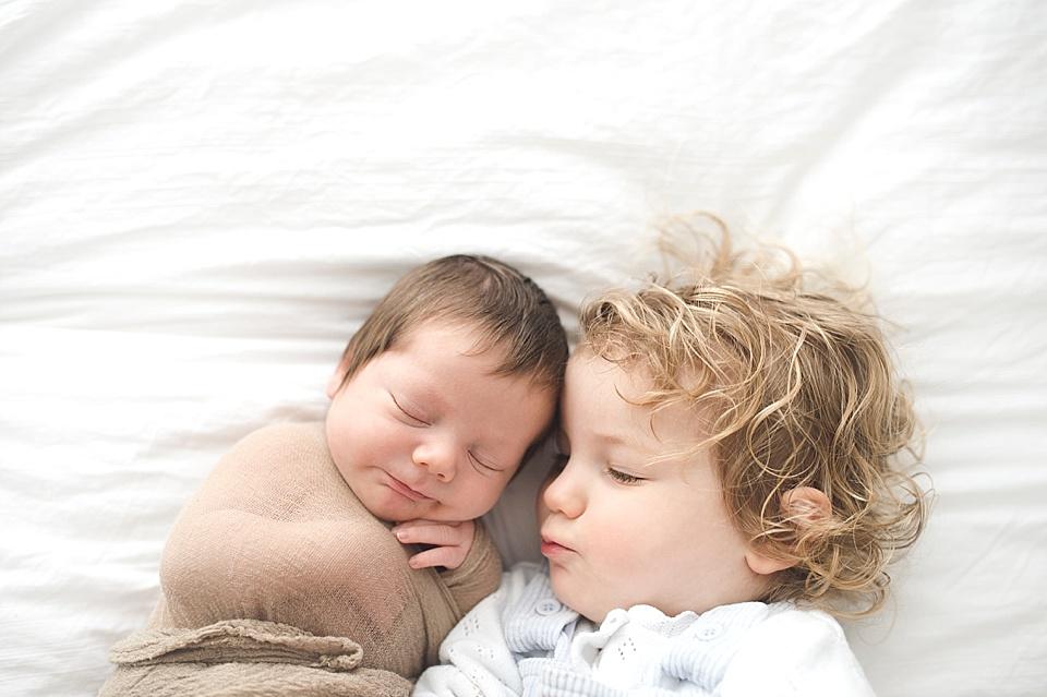 Junge kuschelt mit seinem neuen Bruder