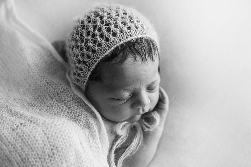 Von einem Tuch zugedecktes Baby mit Wollmütze - schwarzweiß