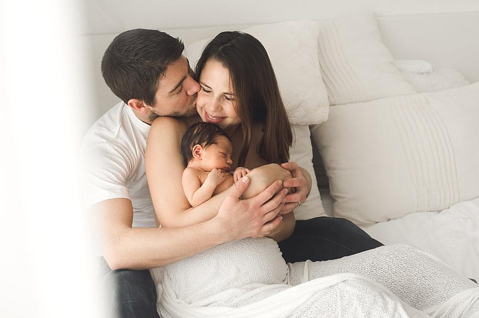 Mann sitzt mit seiner neuen Familie auf dem Bett