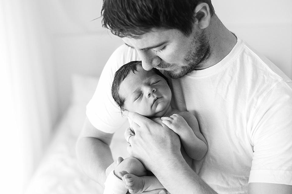 Glücklicher Vater trägt sein neugeborenes Baby - schwarzweiß