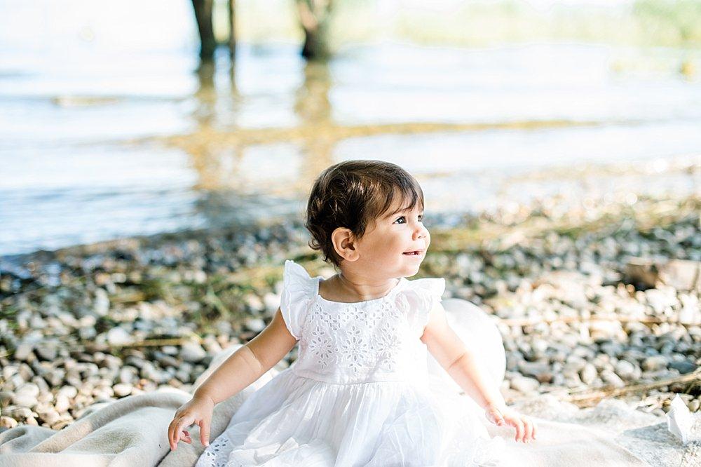 Mädchen sitzt auf einer Decke am Seeufer