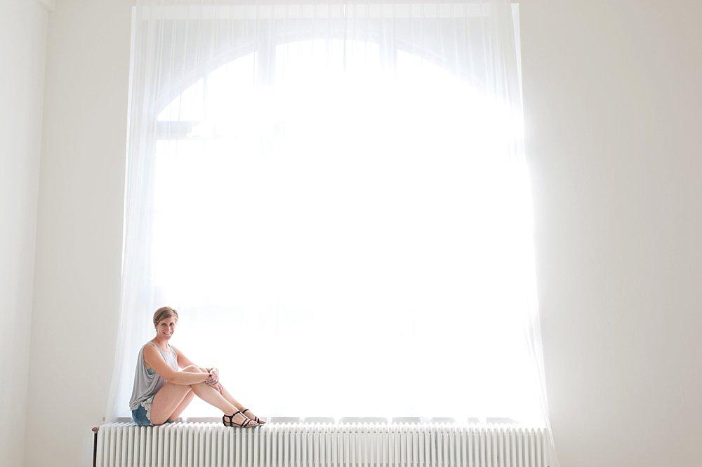 Blonde junge Frau sitzt am Fenster