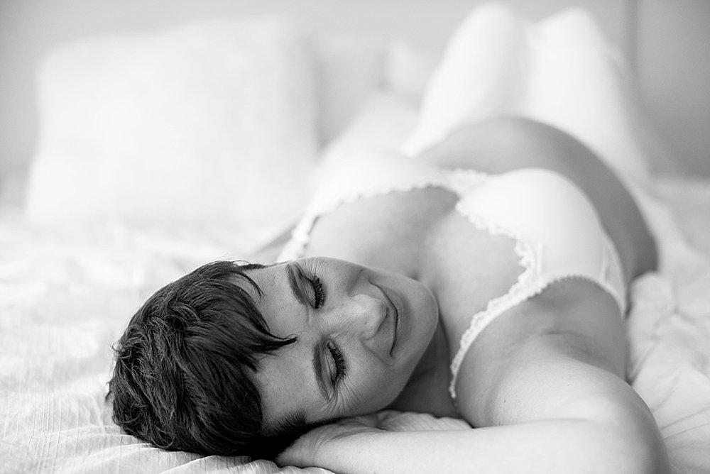 Kurzhaarige Schwangere posiert auf dem Bett - schwarzweiß