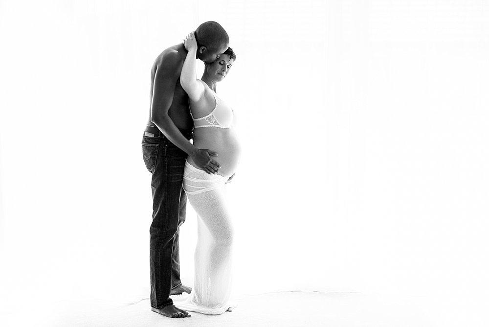 Mann umarmt seine schwangere Partnerin von hinten - schwarzweiß