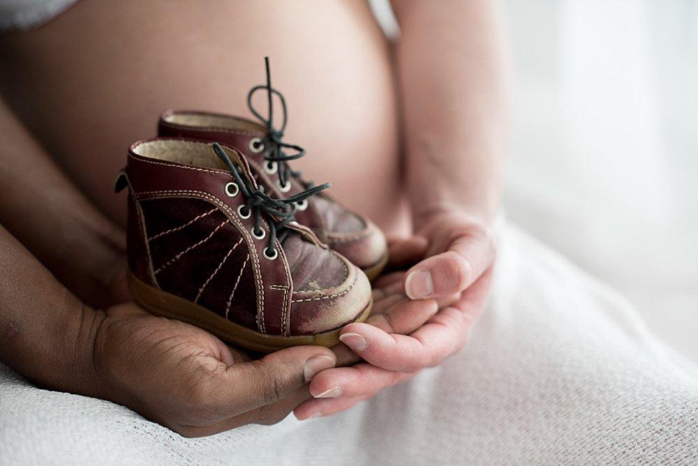 Schwangere hält Babyschuhe in den Händen