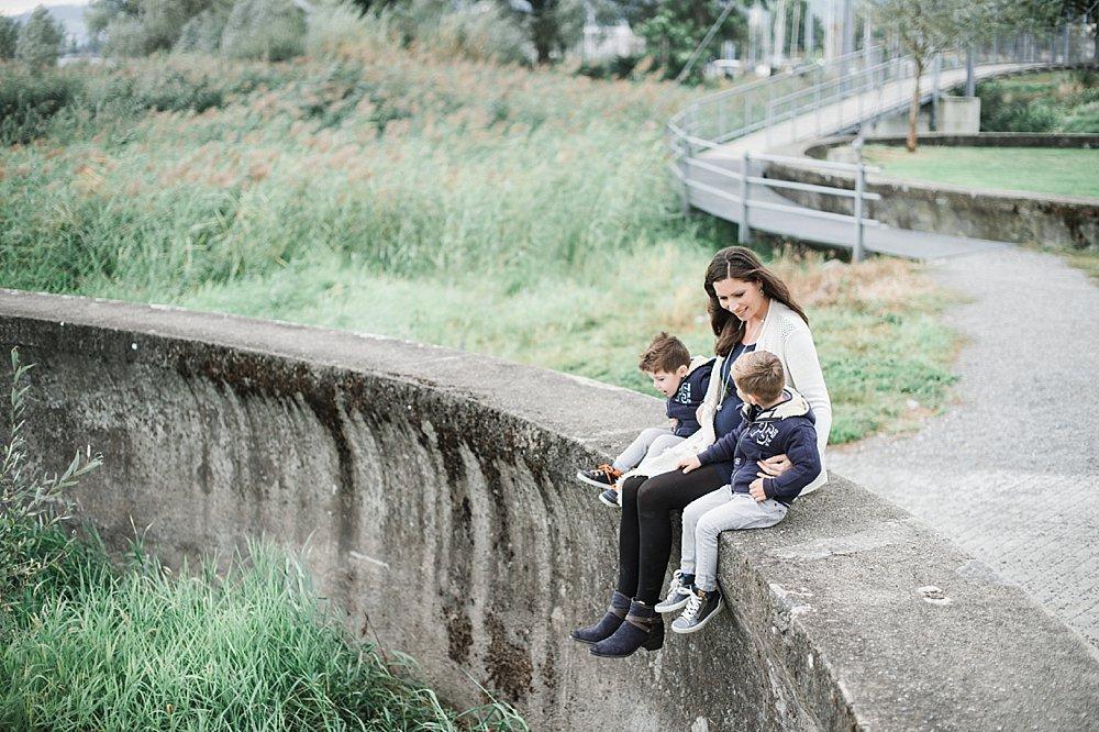 Frau sitzt mit ihren zwei Söhnen auf einer Mauer