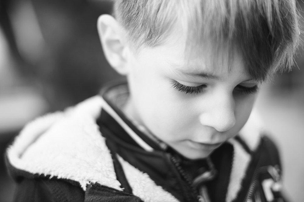 Kleiner Junge schaut nach unten - schwarz weiß Foto