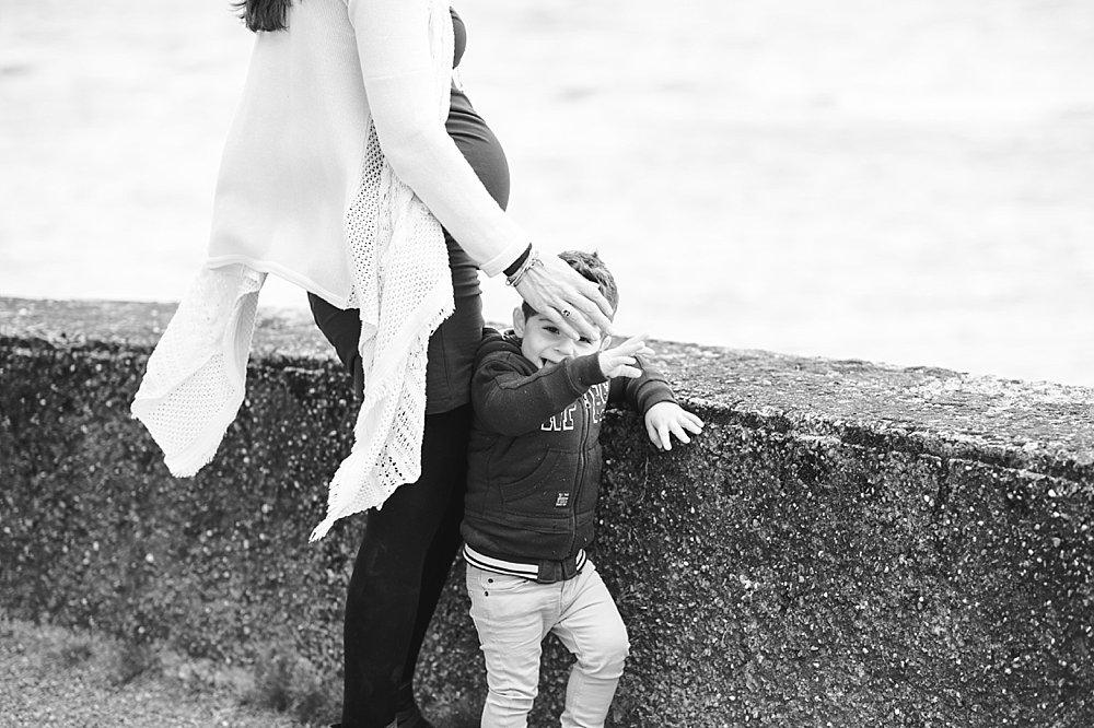 Schwangere Frau steht mit ihrem Sohn an einer Mauer
