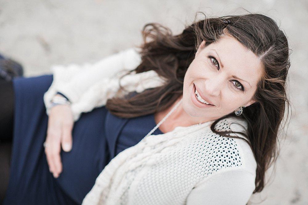 Lächelnde brünnete Schwangere mit weißem Cardigan