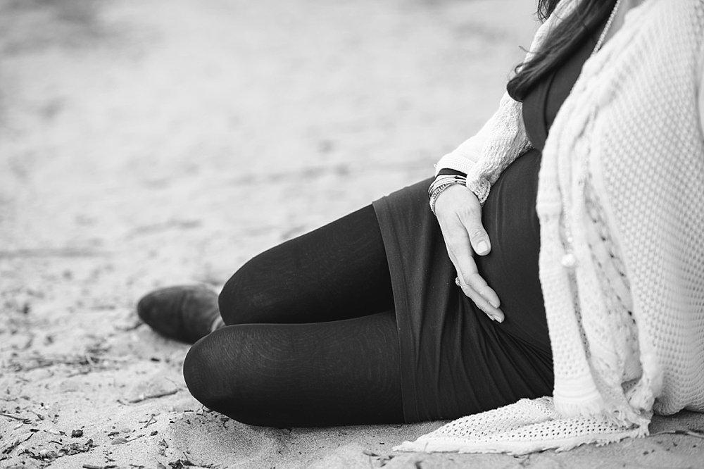 Schwangere Frau sitzt im Sand - schwarzweiß Foto