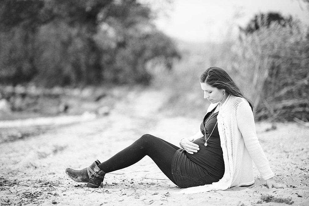 Schwangere junge Frau sitzt im Sand