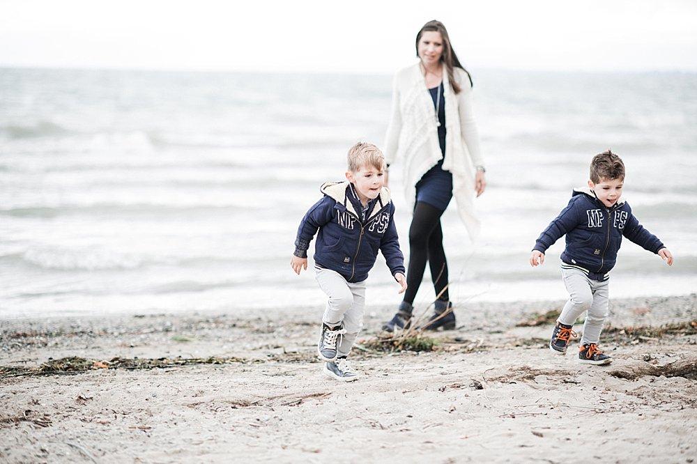 Junge Mutter spaziert mit ihren zwei Söhnen am See