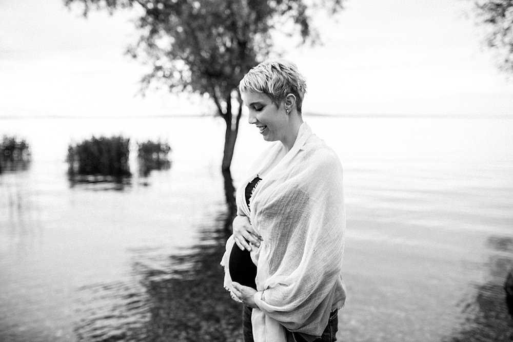 Blonde schwangere Frau steht am See und hält ihren Babybauch
