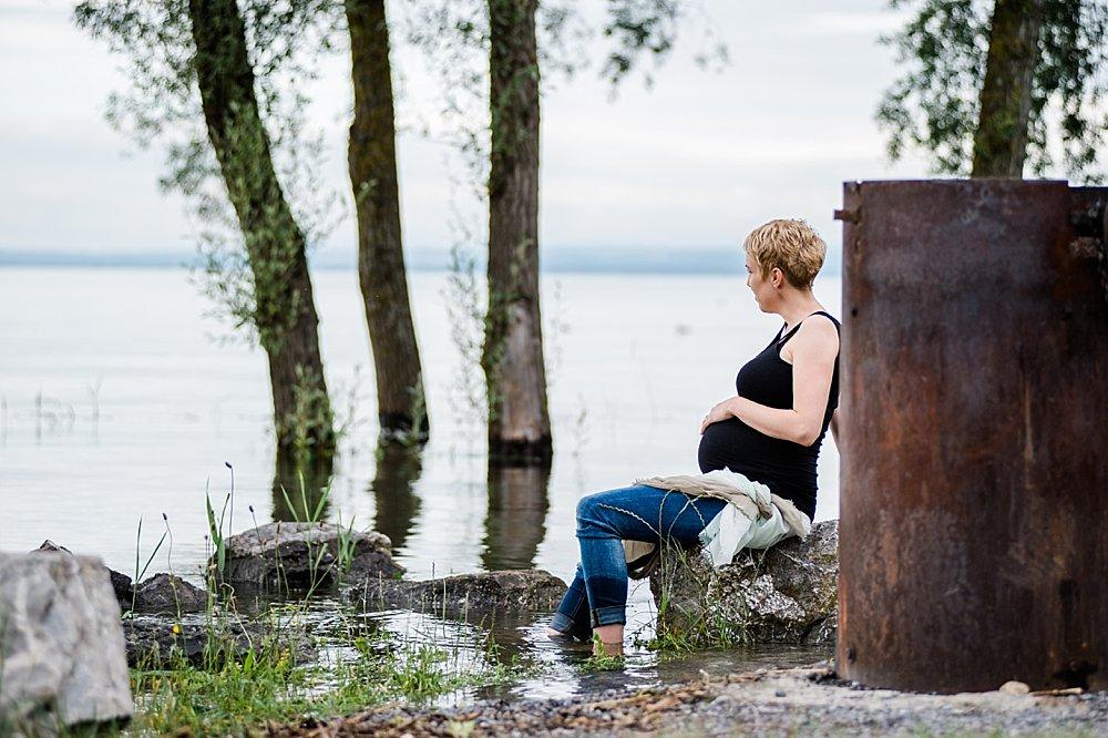 Blonde kurzhaarige Schwangere sitzt auf großem Stein