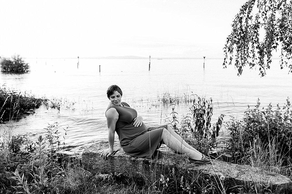 Schwangere Frau posiert am Seeufer - schwarzweiß