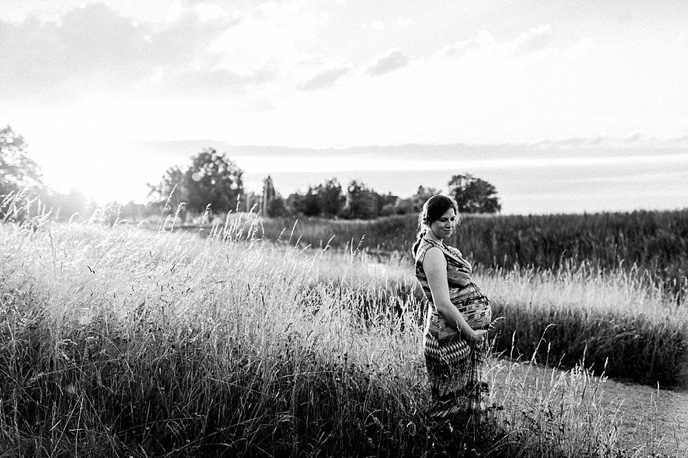 Schwangere Frau steht im Getreidefeld - schwarzweiß