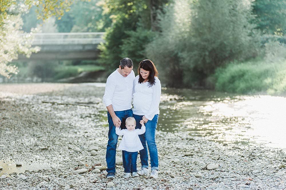 Eltern stehen ihrer Tochter am Flussufer