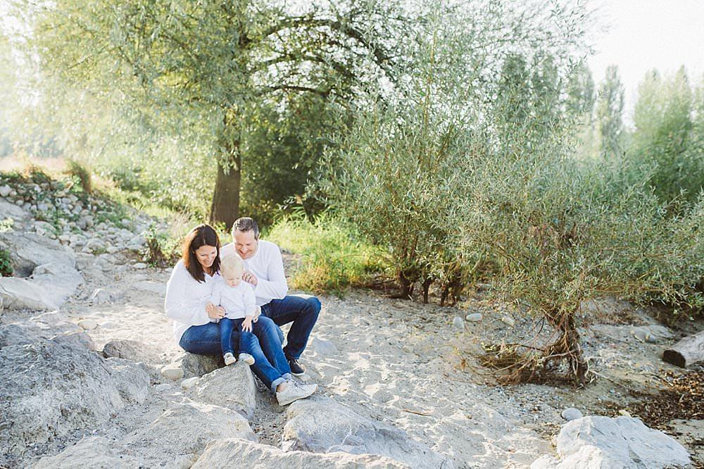 Eltern sitzen mit ihrem Kind im Sand