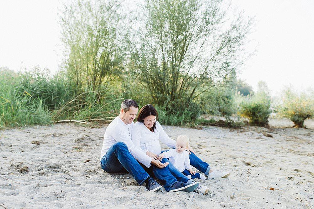 Eltern spielen mit ihrer Tochter im Sand