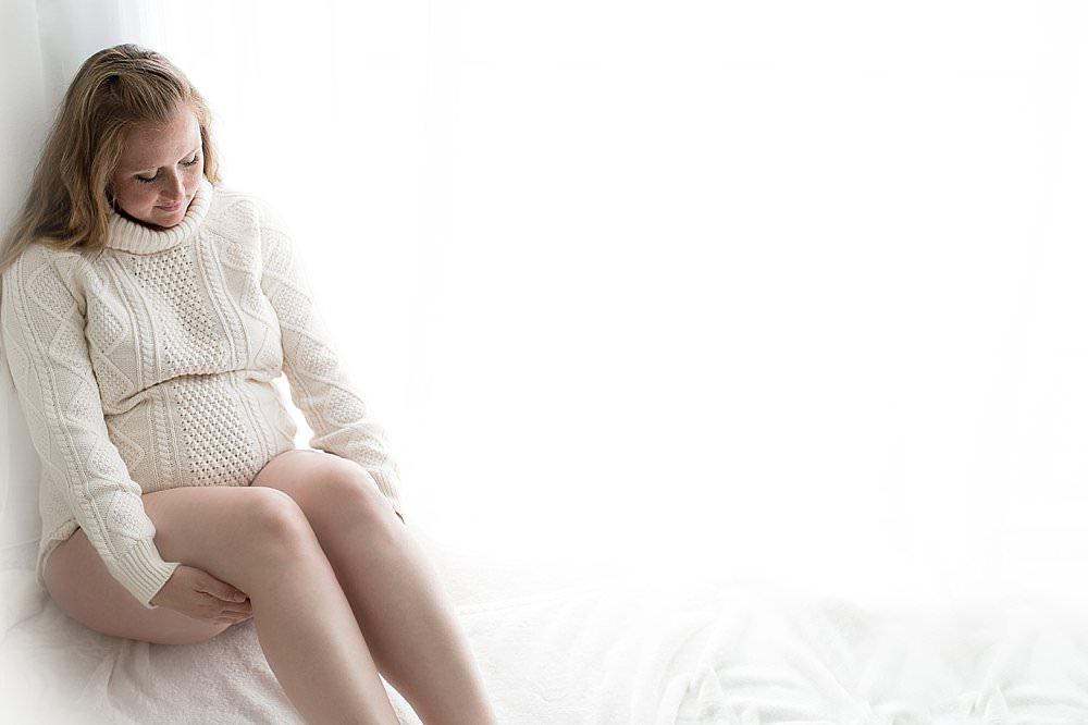Frau in weißem Wollpullover sitzt am Fenster