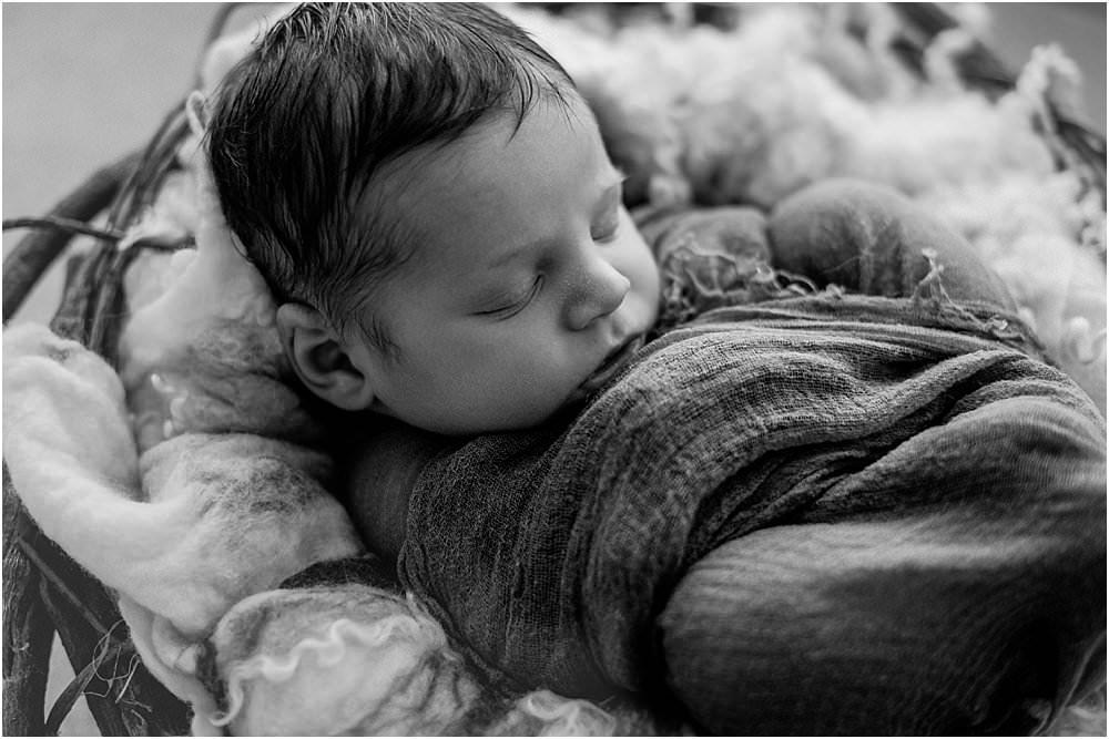 In einem Korb liegendes Baby - schwarzweiß