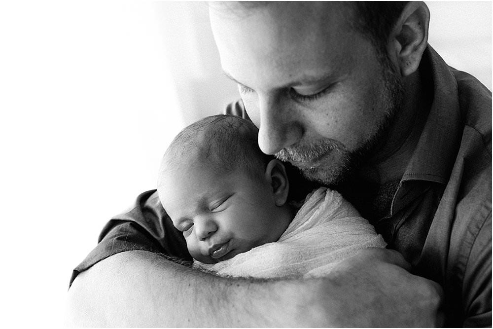 Vater umarmt sein Baby - schwarzweiß