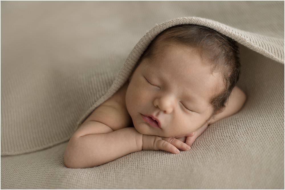 Baby liegt schlafend unter beige-farbener Decke